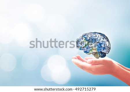World environment day concept: Human hands holding brain of earth over blurred blue nature background. Elements of this image furnished by NASA