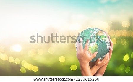 World environment day concept: Human hands holding earth global over blurred green city background. Elements of this image furnished by NASA #1230615250