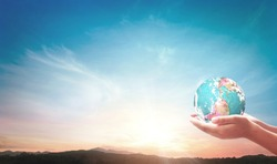 World environment day concept: Human hands holding earth globe on mountain sunset background. Elements of this image furnished by NASA