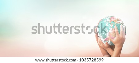 World environment day concept: Many human hands holding earth globe over blurred nature background. Elements of this image furnished by NASA  #1035728599
