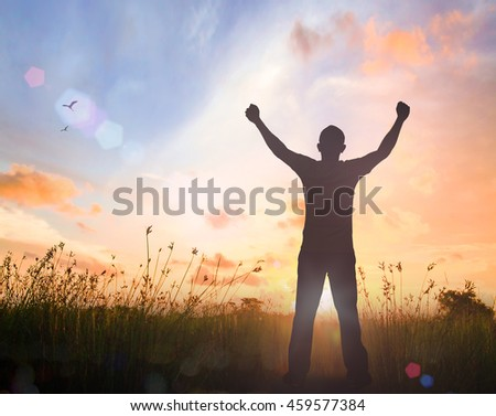 World environment day concept: Silhouette of man raised hands at meadow autumn sunset background