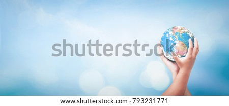 World environment day concept: Two human hands holding earth globe over blurred blue sky and water background. Elements of this image furnished by NASA #793231771