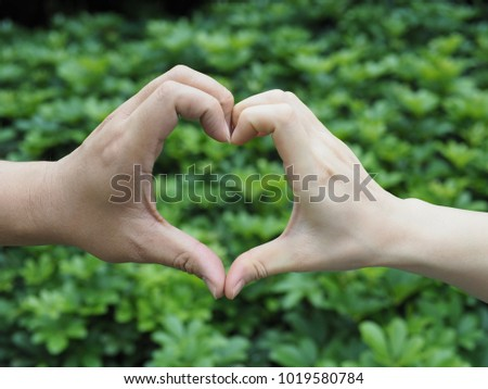 World Environment Day or Valentine concept with heart shaped hand sign of Asian lover. Love hand sign, hand language on blurry green nature background. (selective focus) #1019580784