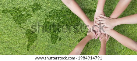 World environment day with global community teamwork, CSR and ESG environmental energy saving collaboration of young children hands stack together on green background for sustainable development goal