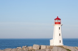 World famous Peggys Cove lighthouse on a sunny day with blue sky.