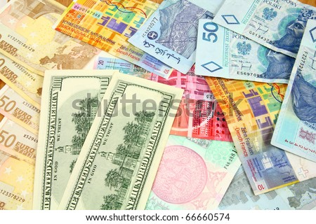 World finance and foreign currency exchange concept - money background with US dollars, Swiss franks, Polish zloty, Euros, Malaysian ringgits and Czech korunas.