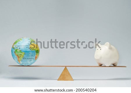 World globe and piggy bank balancing on a seesaw