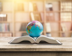 World globe on text book in library