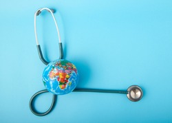 World health day ,Stethoscope wrapped around globe on pastel blue background. Save the wold, Global health care and Green Earth day concept