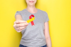 World Hepatitis Day concept. Girl in gray T-shirt holds in her hand awareness symbol red-yellow ribbon. Yellow background