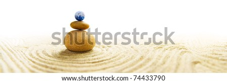 World in balance - Stone pile in a Zen Garden with a miniature Earth globe as topmost stone