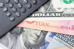 World influenced country, China and USA financial economy, trade war or tariff concept, black calculator on China yuan and US Dollar banknotes, deal for reduce tax on international trading.