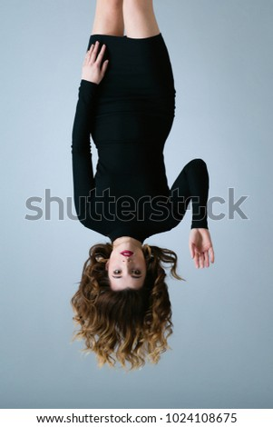 World inside out. The world is upside down. Girl mime in the black dress with red lips. #1024108675