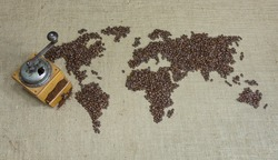 World map with coffee beans and a coffee grinder