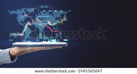 World market trading concept with digital tablet on human hand and digital financial chart graphs and world map on dark background with copyspace. Mockup
