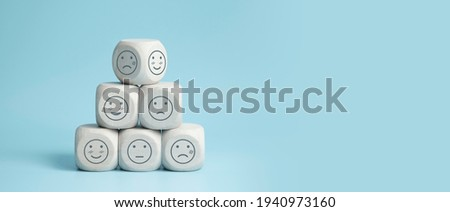 world mental health day concept or feedback rating and positive customer review, wood cube stacking with emotion face icon on blue background