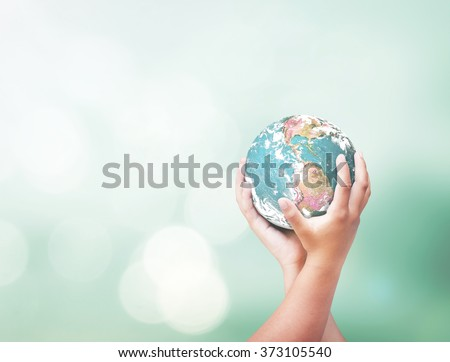 World mission day and CSR concept: Two human hands holding earth globe over blurred nature background. Elements of this image furnished by NASA.