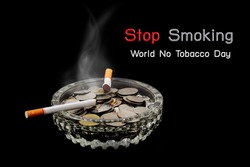 World No Tobacco Day, Cigarette is burning with smoke and coins in ashtray on dark background.