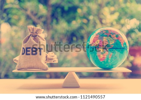 World or global / national debt crisis or imbalance concept : Debt bag, world globe on a balance scale, depicts the government's fiscal profligacy, excessive expenditure or increase public spending. ストックフォト ©