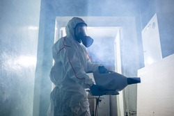 World pandemic COVID-19. professional disinfector in protective suit indoors, kill and remove bacterias from surfaces in isolated space. coronavirus concept