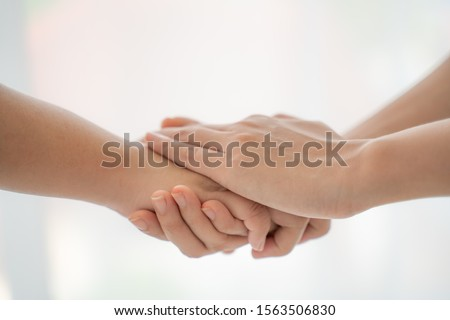 World peace concept.Two people holding hand together over blurred white background with copy space,Business man and woman shaking hands,helping hand.
