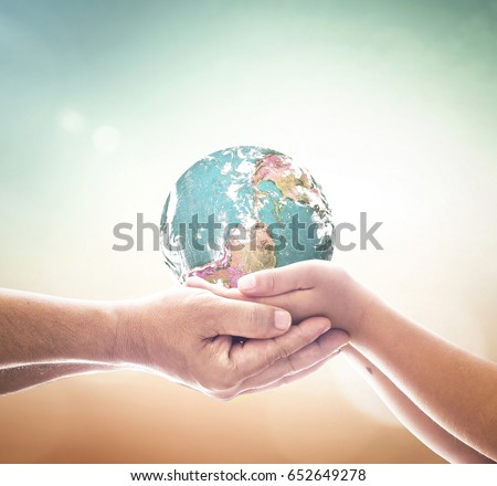 World peace day concept: Children hands holding earth global over blurred abstract nature background. Elements of this image furnished by NASA