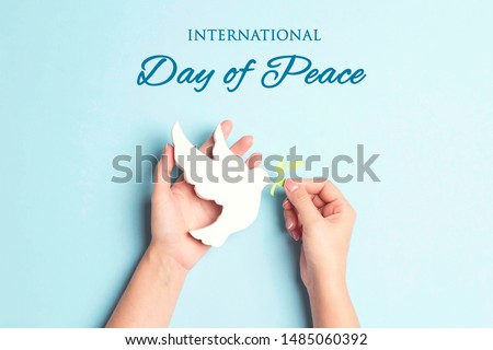 World Peace Day greeting card. Female hands hold dove of peace with olive branch on a blue background. #1485060392