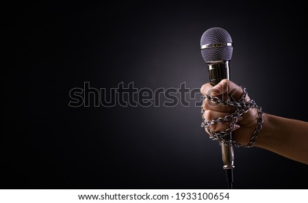 World press freedom day concept. Hand holding a microphone with chain on dark background, symbol of press freedom of speech freedom.