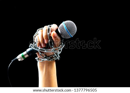 World press freedom day concept. Woman hand with microphone tied with a chain, depicting the idea of freedom of the press or freedom of expression on dark background with copy space for advertisers.