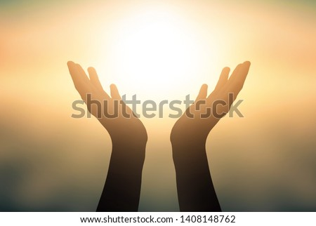 World Refugee Day concept: Raised hands catching sun on sunset sky