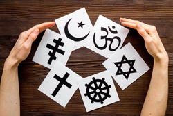 World religions concept. Hands hugs Christianity, Catholicism, Buddhism, Judaism, Islam symbols on wooden background top view