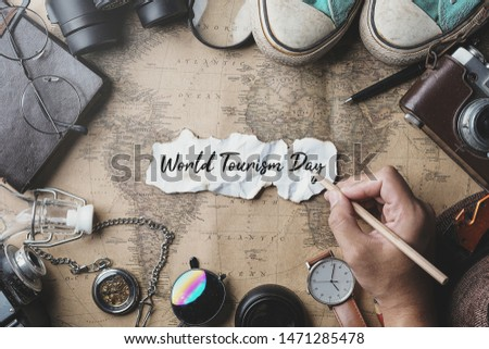 World Tourism Day Hand Writing. Travel Concept Background. Overhead View of Traveler's Accessories on Old Vintage Map #1471285478