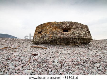 World War Two Pillbox on the Bristol Channel coast at Bossington beach, Somerset ,UK. Built on the pebble beach and camouflaged with pebbles, after seventy years it is undercut but otherwise intact.