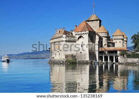 World-wide well-known Ch���¢teau de Chillon on Lake Geneva. The white tourist motor ship floats by a magnificent medieval castle