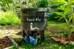 wormery compost bin in organic Australian garden with Feed Me worm sign, sustainable living and zero waste lifestyle