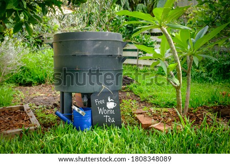 Photo of  wormery compost bin in organic Australian garden with sign for Free Worm Tea, sustainable living and zero waste lifestyle