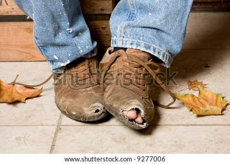 Worn and battered shoes of a beggar in the streets
