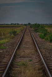 Worn and bent railorad tracks between the fields in Romania. Poor shape of railway tracks through the fields.