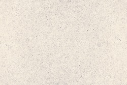 Worn and rough beige background with dots and specks of dust. Grunge texture of antique cardboard