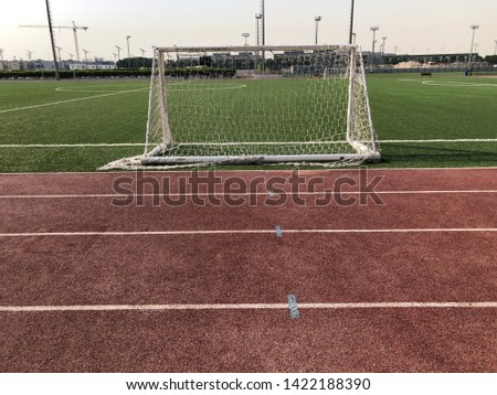 Worn athletics track with a five-a-side football goal.