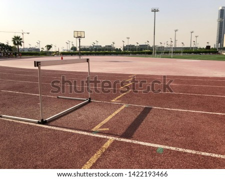 Worn athletics track with a single athletics hurdle within one of the lanes.
