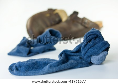 Worn blue socks with slipper om the floor