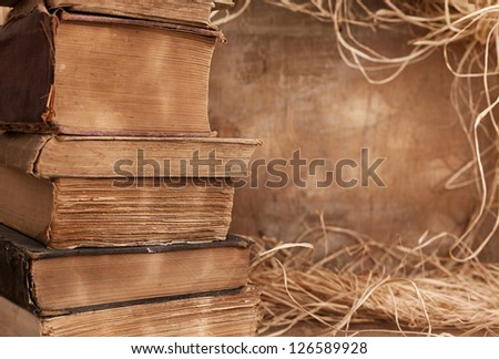worn books over and over on left side of the frame in front of grunge wood background with straw