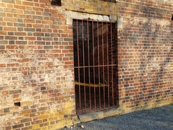 worn brick structure or ruins with metal door or bars