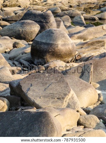 Worn by time and rushing water, these rocks are sculpted by the CT River. Curving and undulating earth toned forms create images for background, wallpaper and other monochromatic uses. #787931500