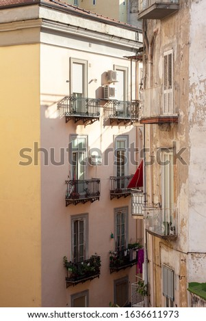 Worn facades of Naples buildings with washed clothes hung out on balconies.