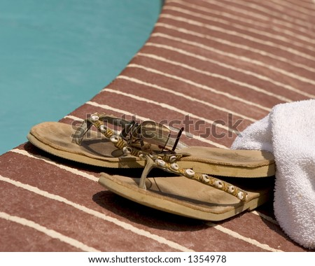 Worn flip-flops and sun glasses laying beside a pool