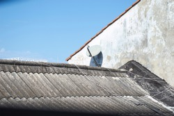 Worn gray and white roof long wired white wall light and television antenna with blue sky