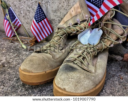 Worn military boots with dog tags and US flags symbolism lost and sacrifice.  #1019007790