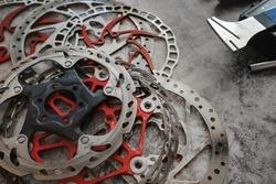Worn mountain bike brake discs lying in the workshop next to the disc straightening tool (rotor truing fork).